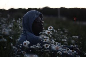 Man picking daisies